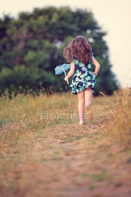 Girl running with butterfly net — Stock Photo