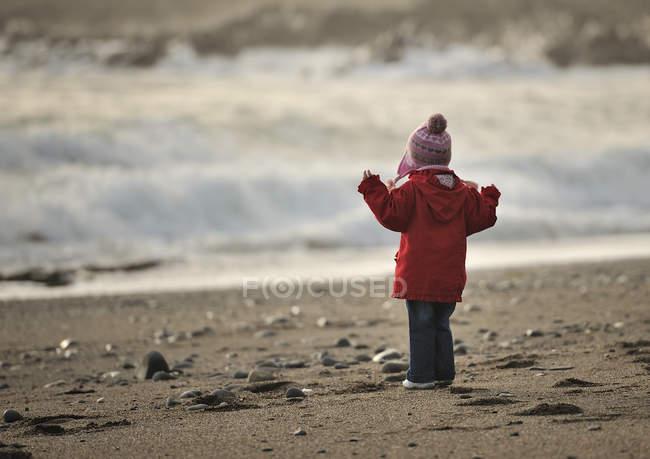 Girl on beach looking at sea — Stock Photo