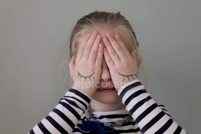 Garota cobrindo os olhos com as mãos — Fotografia de Stock
