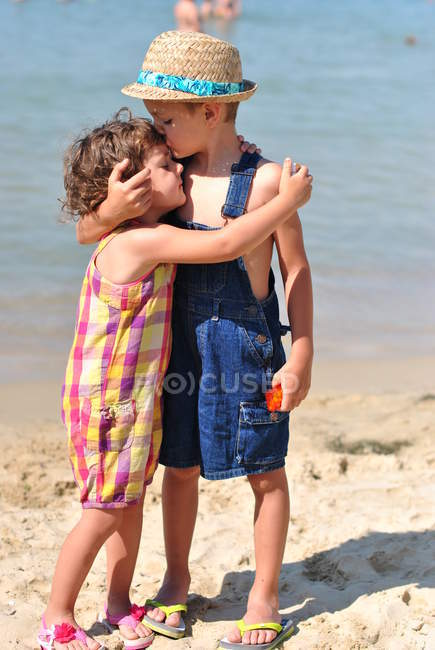 Boy hugging girl on the beach — Stock Photo