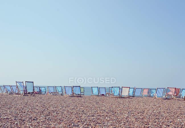 Liegestühle in Reihe am Strand von Brighton — Stockfoto