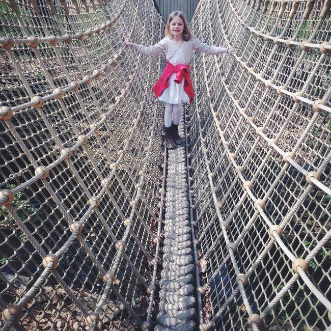 Girl standing on rope bridge — Stock Photo