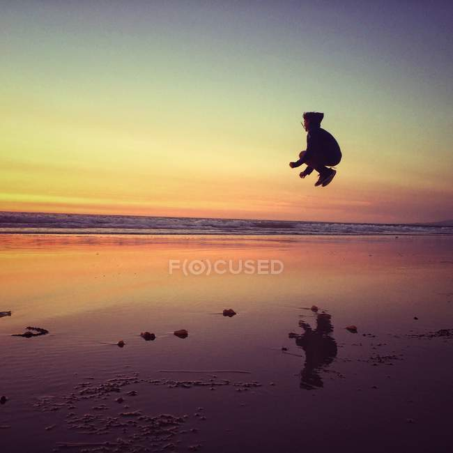 Boy jumping on beach — Stock Photo