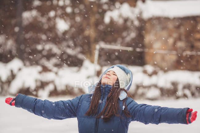 Girl standing in snow looking up — Stock Photo