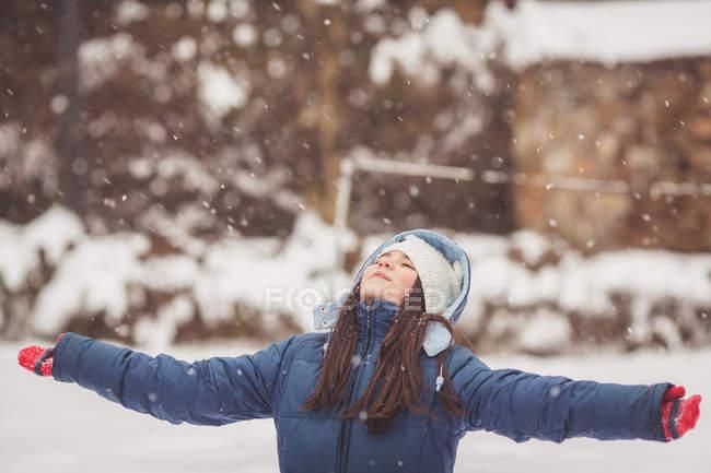 Девушка стоит в снегу и смотрит вверх — стоковое фото