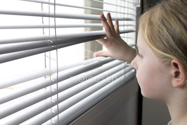 Girl looking through window blinds — Stock Photo