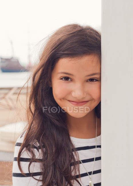 Girl in striped dress smiling on beach — Stock Photo