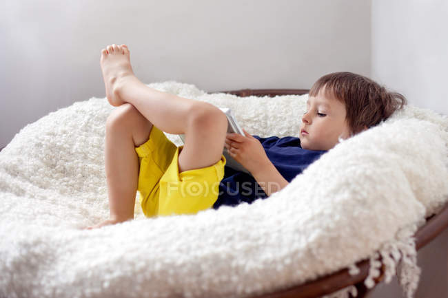Boy lying down in armchair — Stock Photo