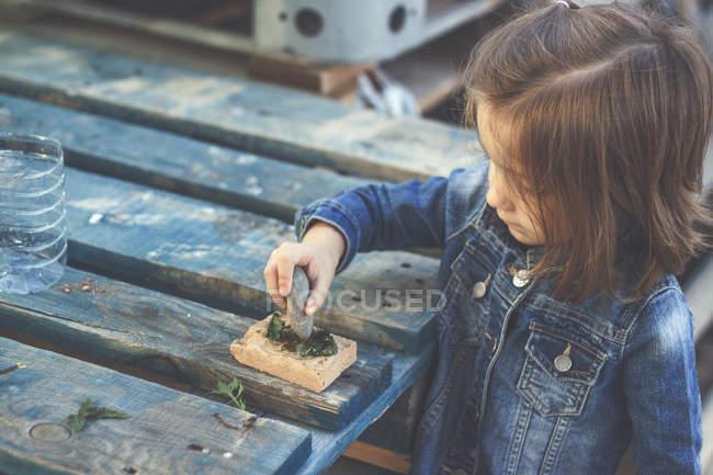 Girl pressing stone against grass — Stock Photo