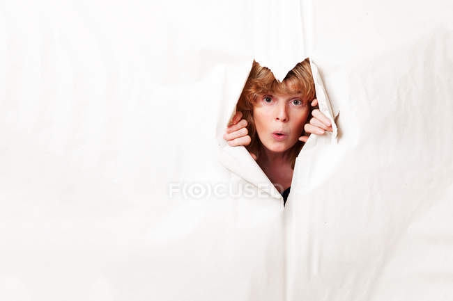 Donna che guarda attraverso la carta strappata — Foto stock