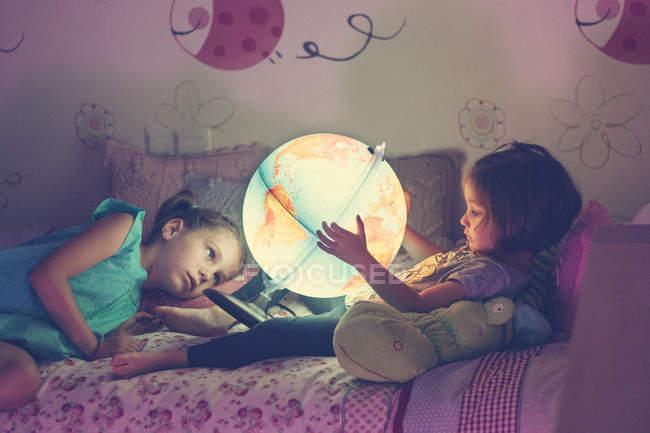 Filles regardant la lampe éclairée — Photo de stock