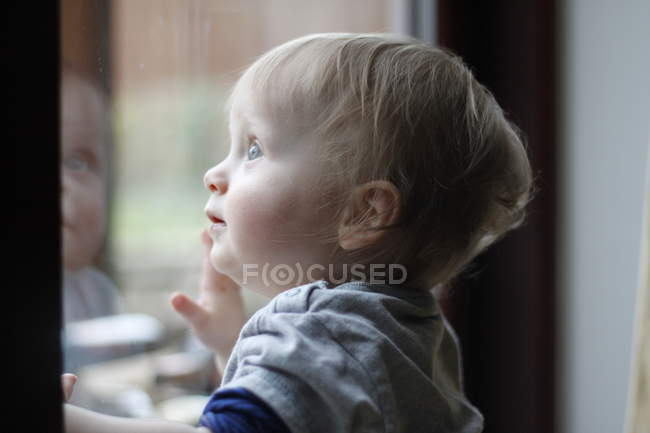 Baby boy looking out of window — Stock Photo