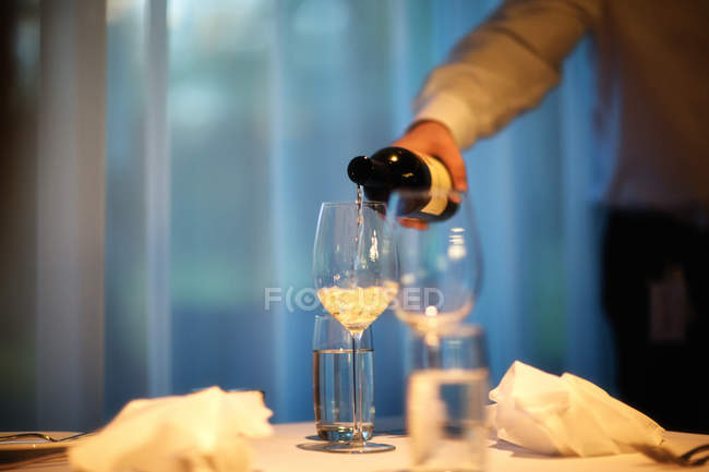 Man pouring white wine in wineglass — Stock Photo