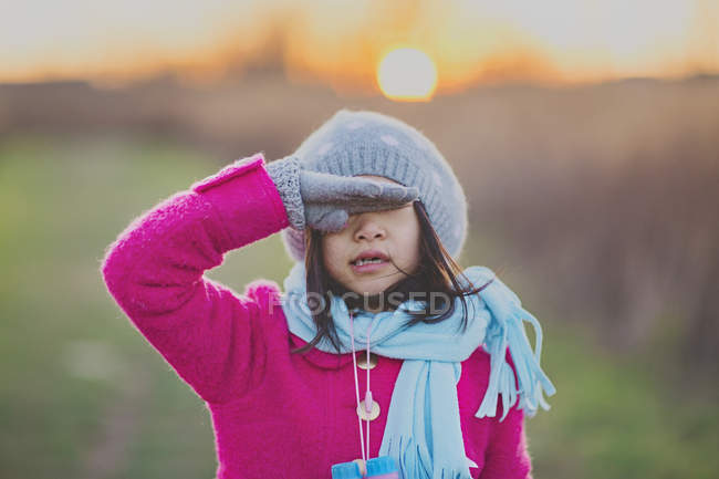 Girl shielding eyes with hand — Stock Photo