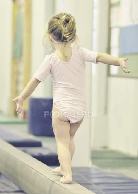 Girl on balance bar — Stock Photo