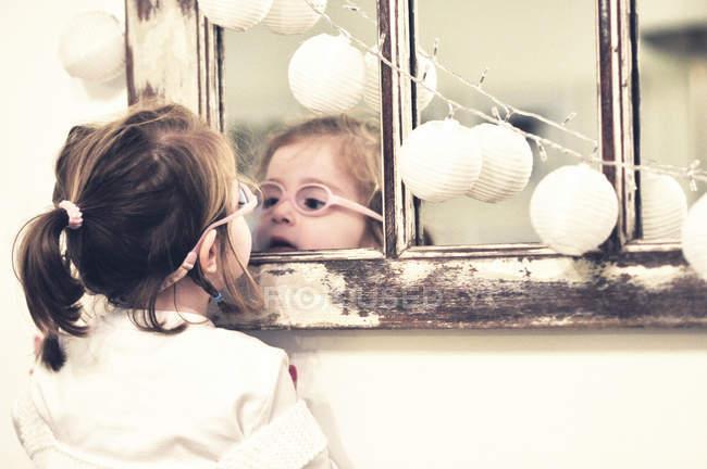 Девушка в очках, смотрящая в зеркало — стоковое фото