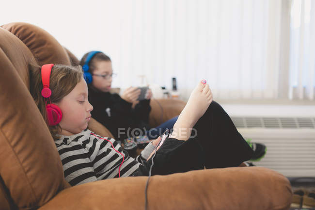 Siblings sitting on sofa with headphones — Stock Photo