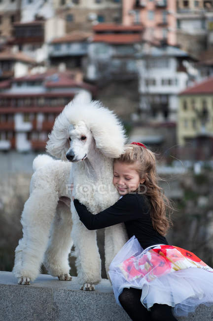 Girl embracing large white poodle — Stock Photo