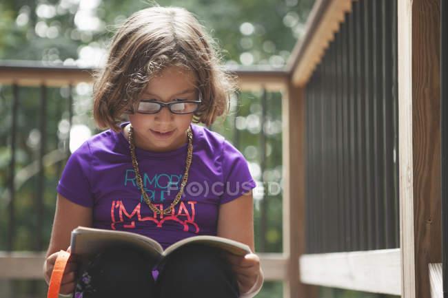 Mädchen-Lesebuch auf Balkon — Stockfoto