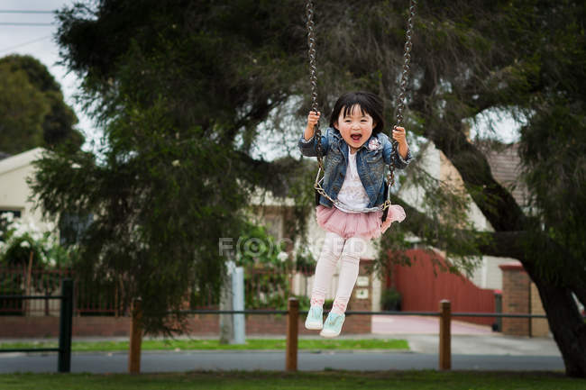 Girl playing on swing in park — Stock Photo