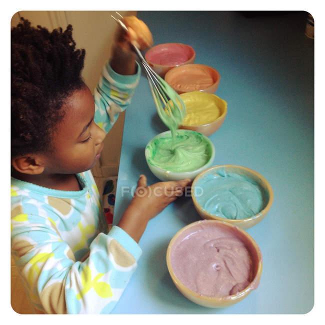 Little girl preparing rainbow cake — Stock Photo