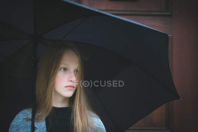 Girl standing under umbrella — Stock Photo