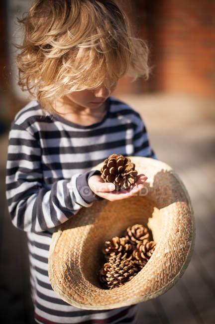 Garçon tenant cône de pin — Photo de stock