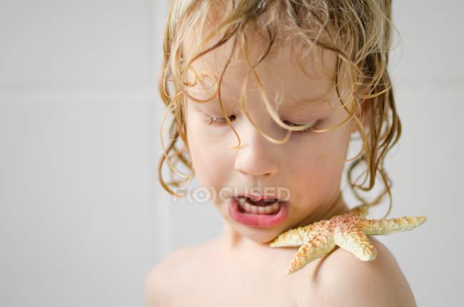 Мальчик со звездной рыбой на плече — стоковое фото