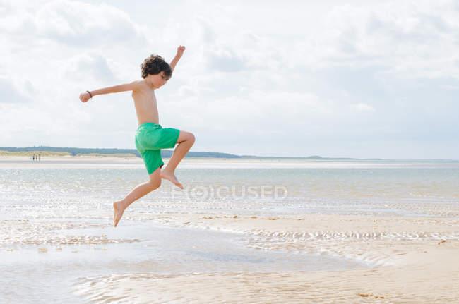 Niño en salto en la playa de arena - foto de stock