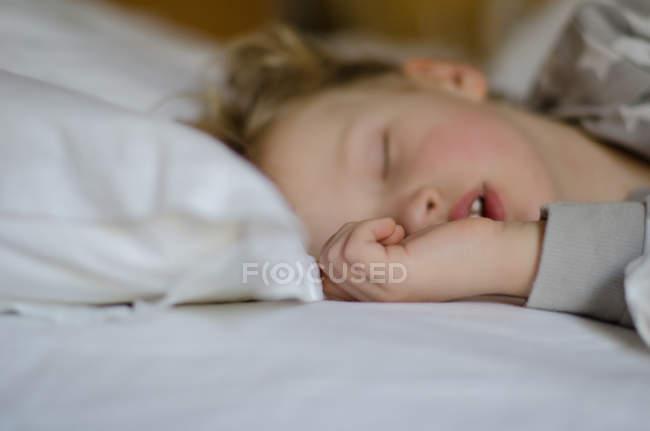 Хлопчик спить в ліжку — стокове фото