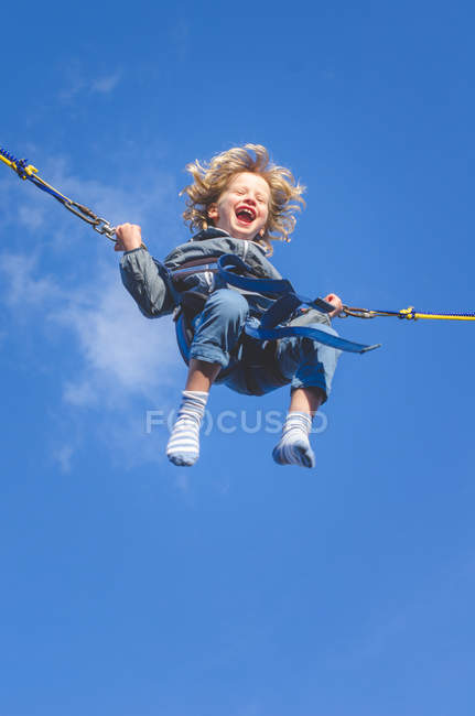 Smiling boy on bungee swing — Stock Photo