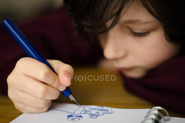 Boy drawing in note pad — Stock Photo