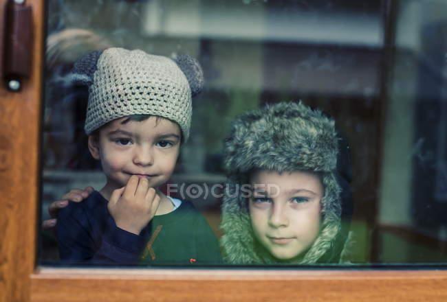 Мальчики смотрят в окно — стоковое фото