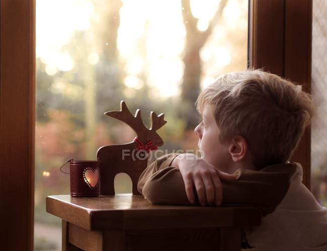 Ragazzo che osserva fuori finestra — Foto stock