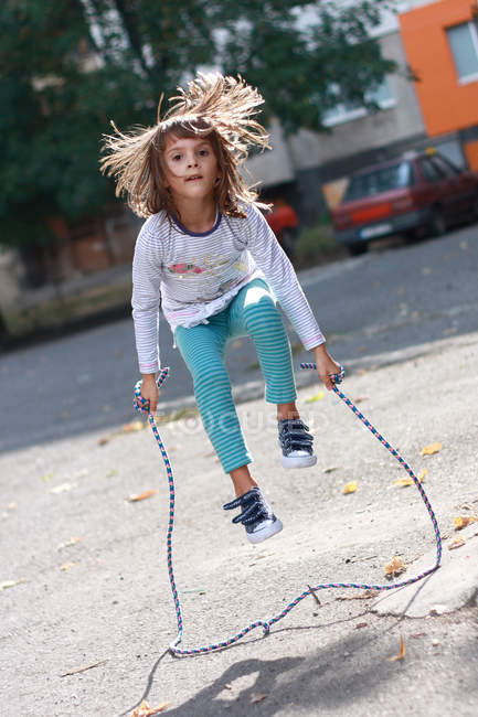 Little girl exercise jumping over rope — Stock Photo
