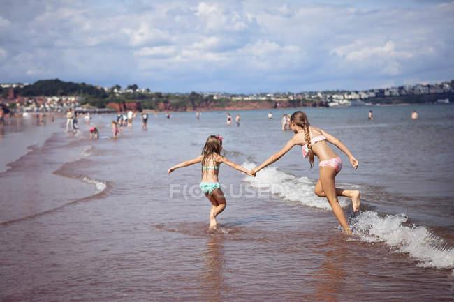 Sisters holding hands run along beach — Stock Photo