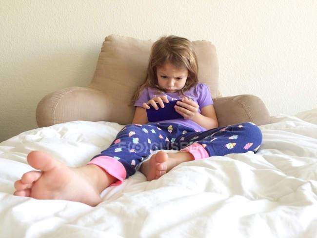 Chica acostada en la cama juega al teléfono inteligente - foto de stock