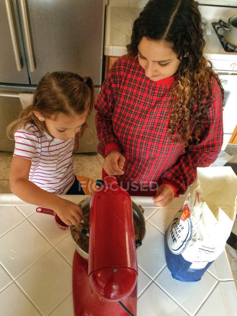 Daughter helping mom in kitchen to cooking — Stock Photo