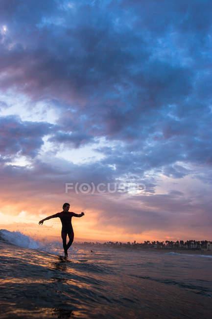 Силуэт серфера на закате — стоковое фото