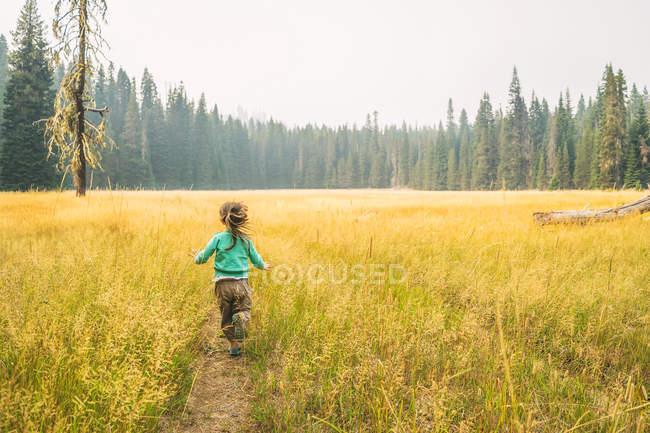 Menina correndo para baixo pista — Fotografia de Stock