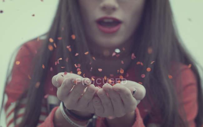 Menina, soprando confete — Fotografia de Stock