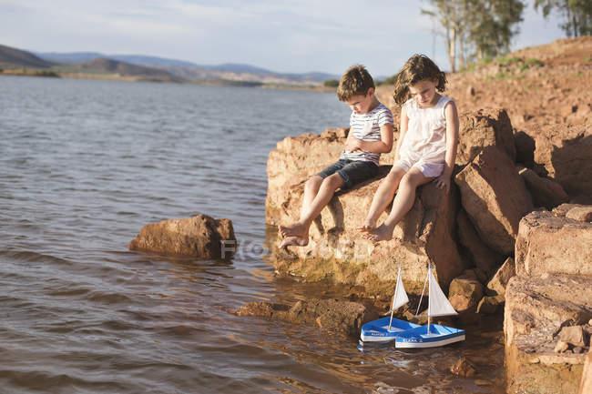 Хлопчик і дівчинка, що сидить на рок — стокове фото