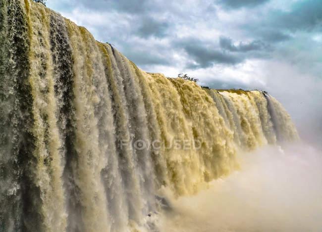 Powerful stream waterfall on border — стокове фото