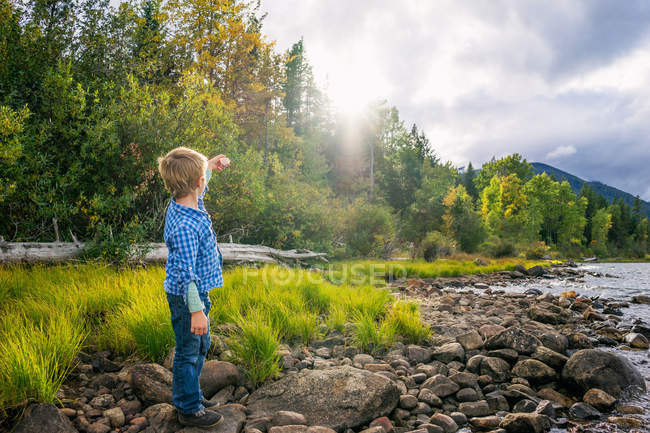 Boy pointing hand lens on sun — Stock Photo