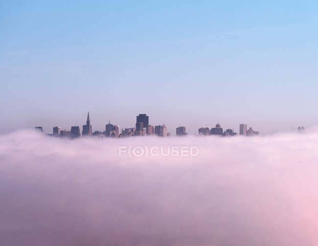 Skyscrapers seen above fluffy clouds — Stock Photo