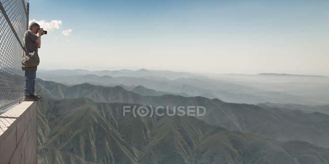 Photographer making photos of mountains — Stock Photo