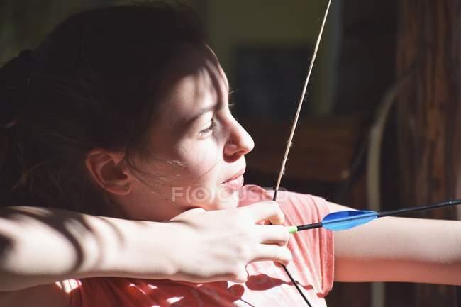 Молодая девушка играет в стрельбу из лука — стоковое фото