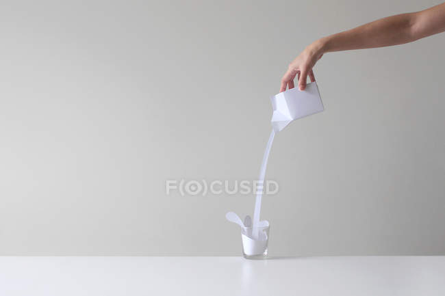 Hand of woman pouring milk — Stock Photo