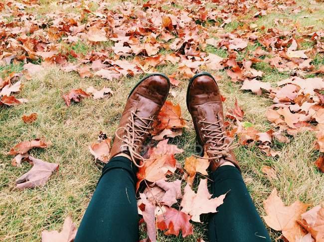 Botas femininas descansando sobre folhas — Fotografia de Stock