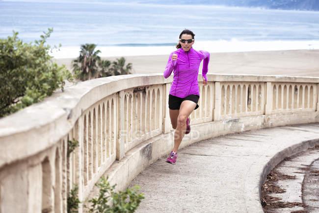 Mulher subindo o passeio pela praia — Fotografia de Stock
